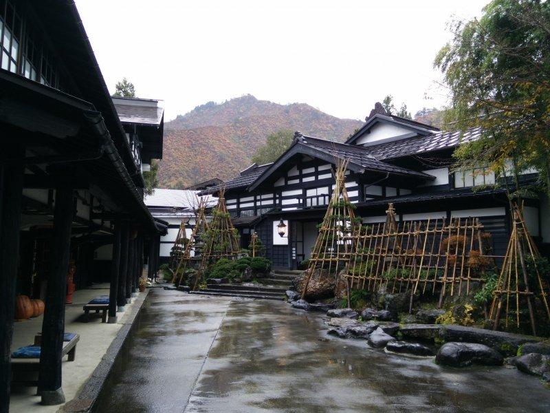 Das Ryugon Ryokan mit den Bergen von Mukaimachi im Hintergrund.
